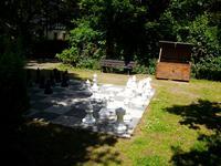 Ansicht auf die Freischachanlage im Grünen mit zirka 60 cm hohen Schachfiguren (hier weiße Schachgfiguren im Vordergrund). Im Hintergund eine Bank zum Verweilen