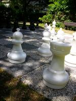Ansicht auf die Freischachanlage im Grünen mit zirka 1 Meter hohen Schachfiguren (hier weiße Schachgfiguren im Vordergrund). Im Hintergund eine Bank zum Verweilen.